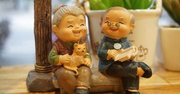 Tiny grandma and grandpa figurines sit next to one another laughing, stroking a cat, and reading the paper.