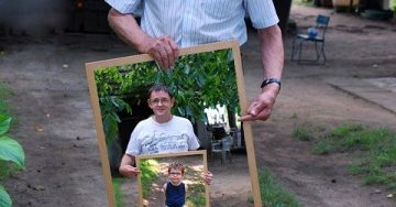 A grandpa holds a picture frame of his son who holds a picture frame of his son. Generations!