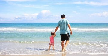 A father walks along the shoreline of a beach with his toddler in hand. Barefoot, they walk in the beautiful blue ocean water.