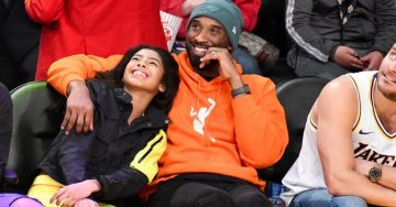 Kobe Bryant sits in the stands of a basketball game, his arm around his daughter.