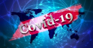 """A map of the globe with a """"Covid-19"""" banner across it"""