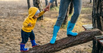 A woman in bright blue rain boots carefully helps a toddler, also in blue rainboots, walk across a fallan log ramp. He wears a bright yellow jacket with the hood over his head.