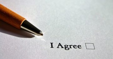 """A page reads """"I Agree"""" with an empty square beside the words. A pen awaits use to check the box."""