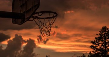 A bright orange sunset sky is the backdrop for a deserted looking basketball net.
