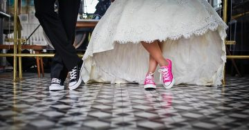 From the knees down, a bride and groom are showing off their cool sneakers. Hers are pink and his are black.