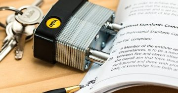 A padlock and keys are fitted into the punch holes of several pages of a document.