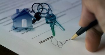 A legal document that requires a signature lays on a table with a set of house keys on top as a hand signs for the new home!