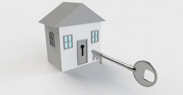 An animated house with a giant, oversized key being fit into the front door.