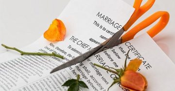 "A document titled ""marriage certificate"" is being cut in half by a pair of orange scissors while an orange rose of equal vibrancy lays across the document - a victim of the scissors."