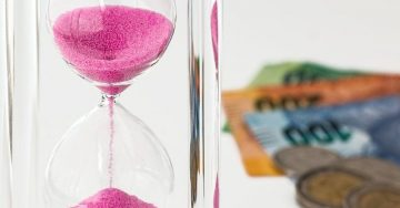 In the foreground, an hourglass with bright pink sand is about half way emptied. In the background is money from different countries.