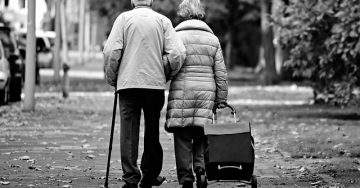 An elderly couple walk hand in hand down the sidewalk. They are wearing coats. The woman pulls along a rolly bag and the gentleman has a cane.