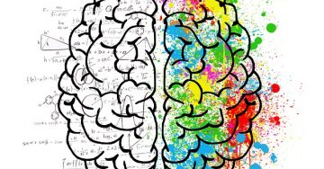 An image of a brain half black and white and half splotched with bright colors as well as a bunch of complicated math equations. A depiction of intellect.