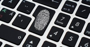 A close up of a keyboard with a thumb print over one key to indicate security for digital assets.