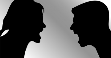Two shadows of black faces yelling at each other against a gray background.