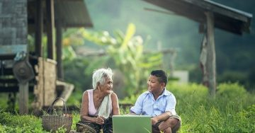 An older woman and young man sit outside in the grass looking at a computer.