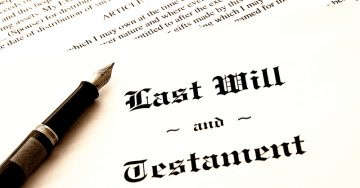 Last Will and Testament cover page with a calligraphy pen laying across the document..