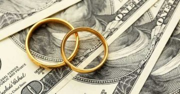 Two gold wedding rings on top of hundred dollar bills.