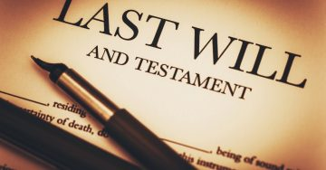 A yellow document that says last will and testament with a pen laying across it.