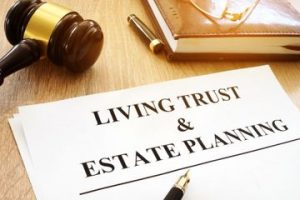 """A document titled """"Living Trust & Estate Planning"""" lays on a table with a pen, gavel, and a book."""