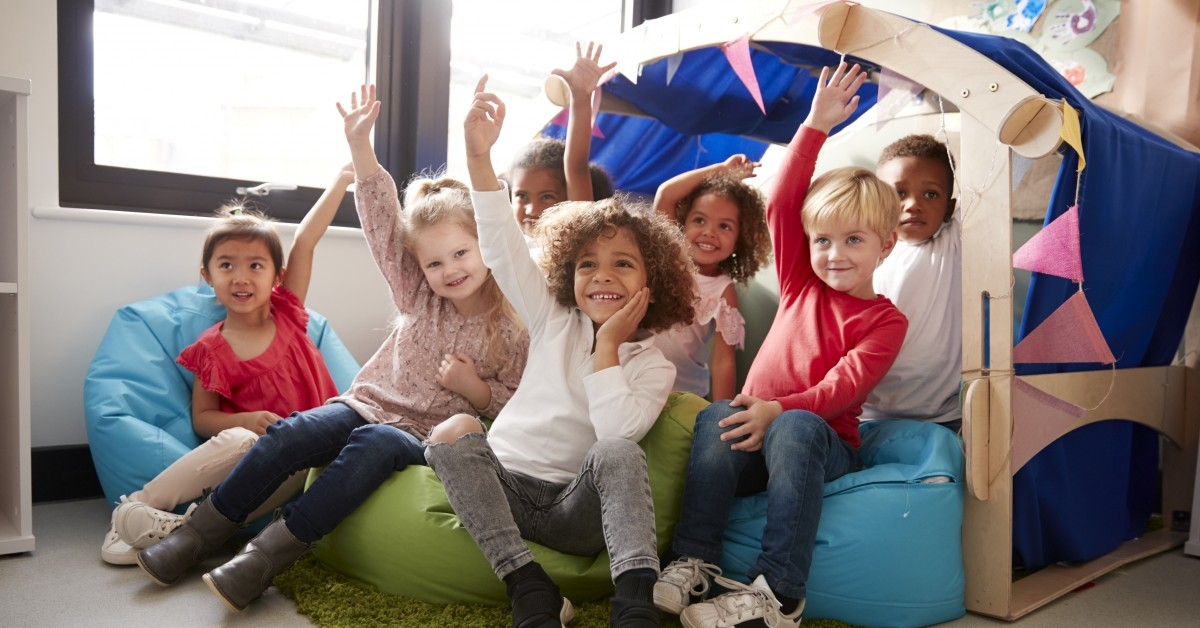Featured image of children sitting in front of a tent and raising their hands.