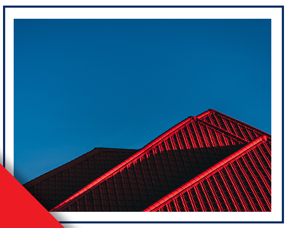Red and black rooftop of property shown with blue sky in background. Photo courtesy of Robin Kutesa on Unsplash.
