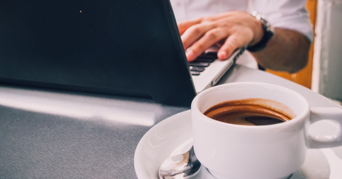 Photo of someone drinking coffee next to a computer by AndriyKo Podilnyk on Unsplash