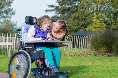 Certified Nursing Assistant aiding a pediatric patient in a wheelchair