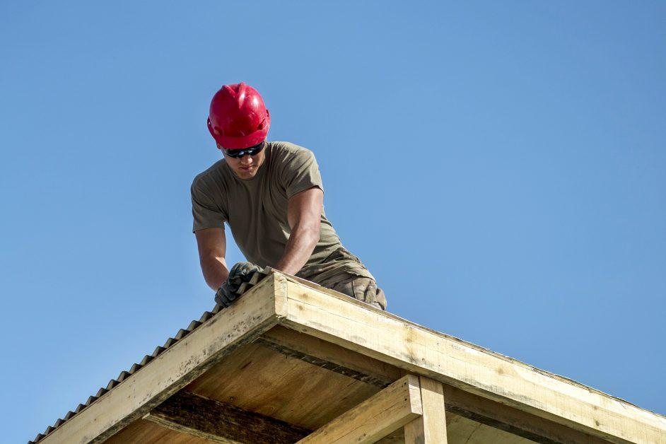 A roofer installs sheet metal on a home. Creator: Senior Airman Sean Carnes | Credit: NATO Special Operations Componen Copyright: Public Domain
