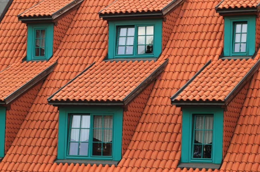 A house with teal accents on the windows and a burnt orange, terracotta tiled roof.