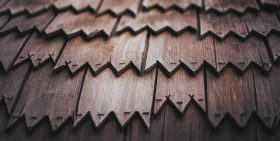A roof covered with wooden shingles. Photo by Tim Mossholder on Unsplash.