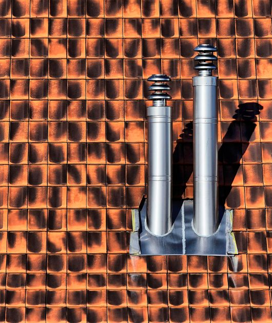 The gray stainless steel exhaust pipes on a shingle roof. Photo by Ricardo Gomez Angel on Unsplash.