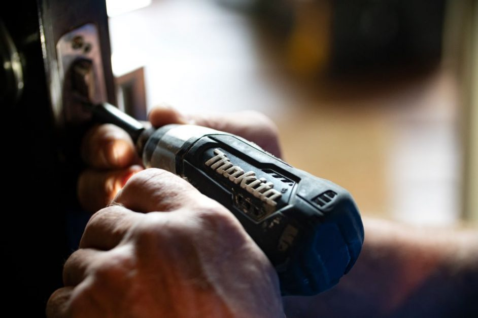 A close-up photo of a man using a black power drill to secure a screw to an out-of-focus object. Photo by Theme Photos on Unsplash.