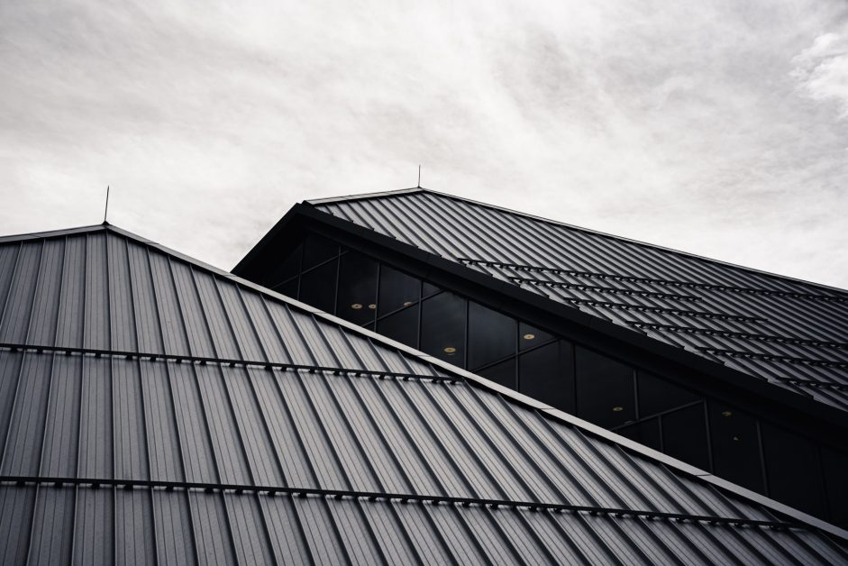 Black metal roof on a glass building with white trim.