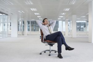 office-worker-sitting-in-swivel-chair-hands-behind-head-in-empty-office-space