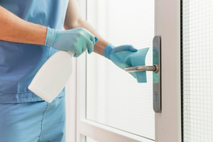 A man cleaning a doorknob with a cloth