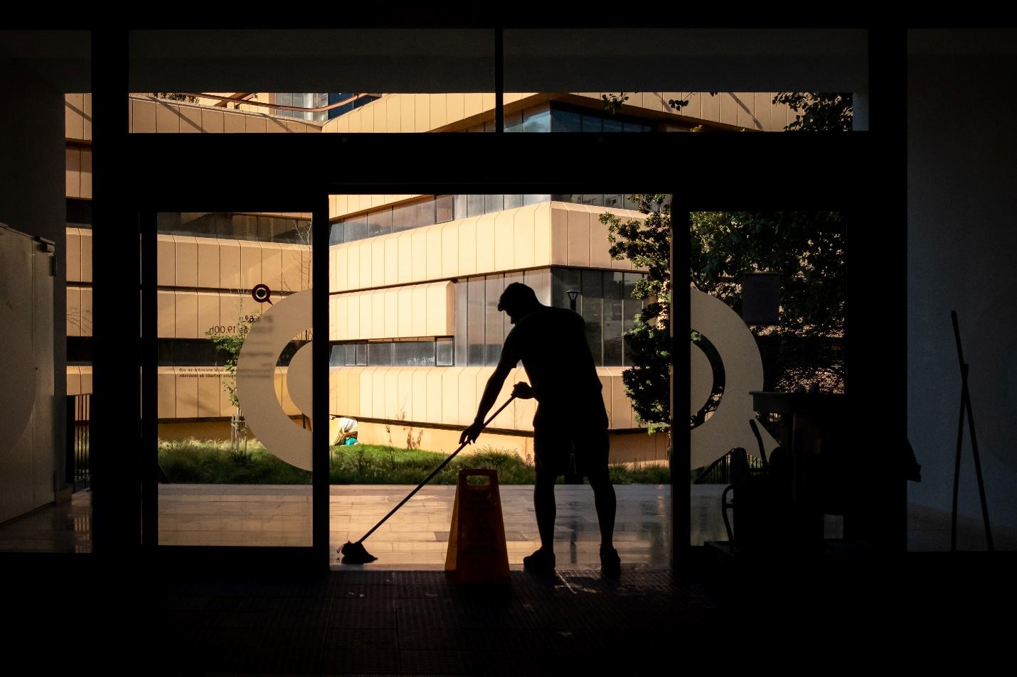 Man cleans entrance of a building
