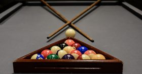 A picture of a pool table with balls in triangle and crossing pool cues