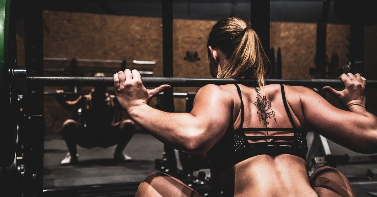 A woman performs a barbell squat. Photo by Sven Mieke on Unsplash.
