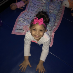 Smiling girl lying on dance mat and blanket - Fancy Feet Dance