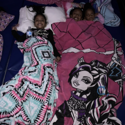 Three smiling girls in sleeping bags on dance mat - Fancy Feet Dance