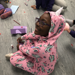 Girl in glasses and pajamas sitting on floor - Fancy Feet Dance