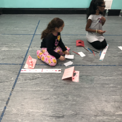 Two girls sitting on floor, doing arts and crafts - Fancy Feet Dance
