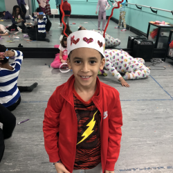 Boy in red jacket wearing a paper headband - Fancy Feet Dance