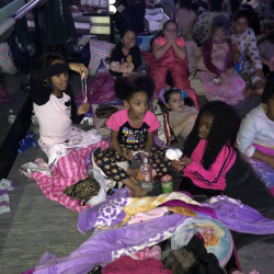 Group of girls sitting on floor, watching a movie - Fancy Feet Dance
