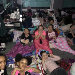 Group of girls relaxing on floor and smiling at camera - Fancy Feet Dance