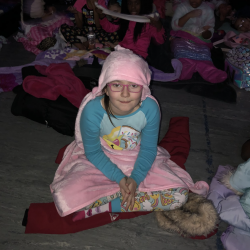 Girl in glasses and pajamas, wrapped in blanket and sitting on floor - Fancy Feet Dance