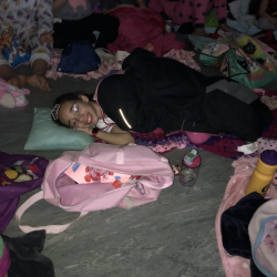 Girl in glasses, lying on floor in sleeping bag - Fancy Feet Dance