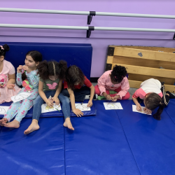 Group of girls sitting on floor mat, coloring on paper - Fancy Feet Dance