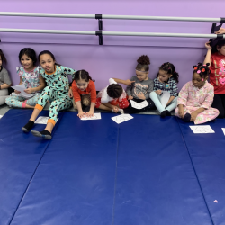 Group of girls sitting on dance mat with drawings - Fancy Feet Dance