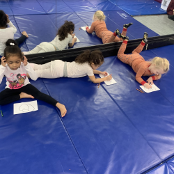 Three girls sitting on dance mat, drawing pictures - Fanct Feet Dance